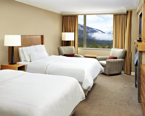 A well furnished bedroom with two beds and a television alongside the mountain view.