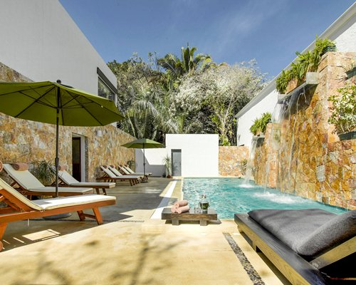 Grotto pool with chaise lounge chairs and sunshades.