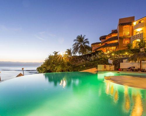 View of Grand Palladium Vallarta and outdoor swimming pool alongside the ocean.
