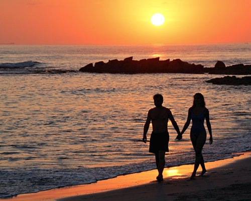 A couple walking on the beach at dusk.