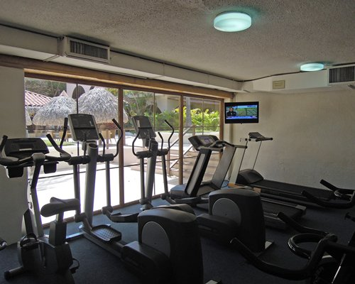A well equipped indoor fitness area with a television and an outside view.