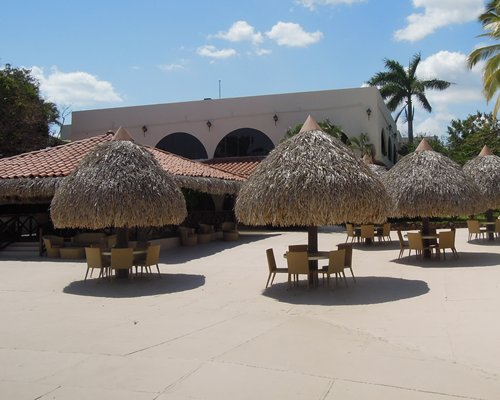 A view of patio furniture with thatched sunshades.