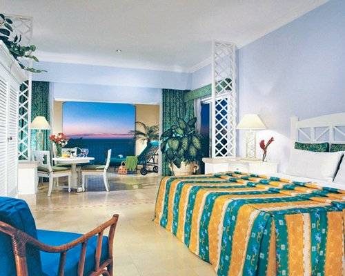 A well furnished bedroom with dining area chaise lounge chairs balcony and ocean view.