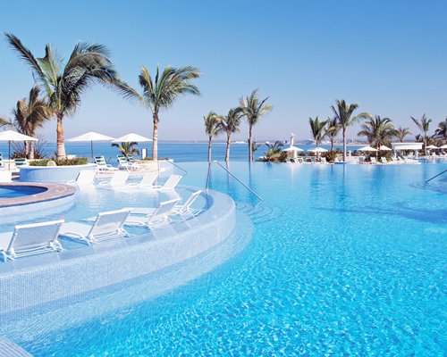 An outdoor swimming pool with chaise lounge chairs and sunshades alongside the ocean.