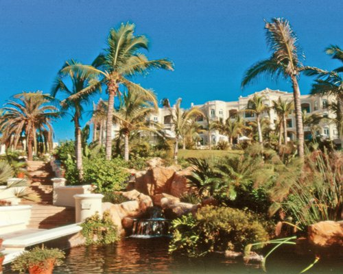 Scenic exterior view of Pueblo Bonito Resort alongside the waterfront with grotto waterfall and a pathway.