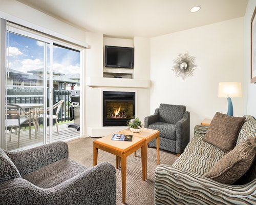 A well furnished living room with a television fire in the fireplace and balcony.