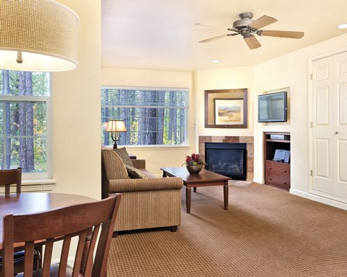 An open plan living dining and bedroom with a television and fireplace.