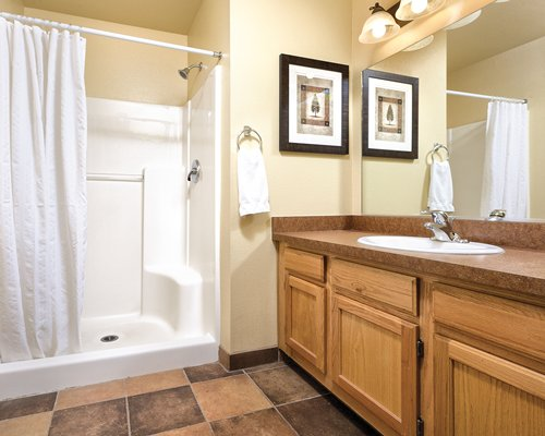 A bathroom with shower and a single sink vanity.