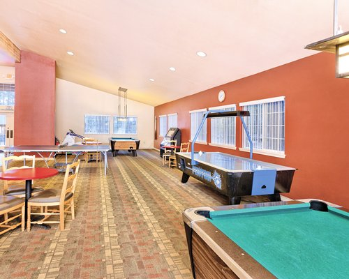 A recreational room with pool tables ping pong and arcade game.
