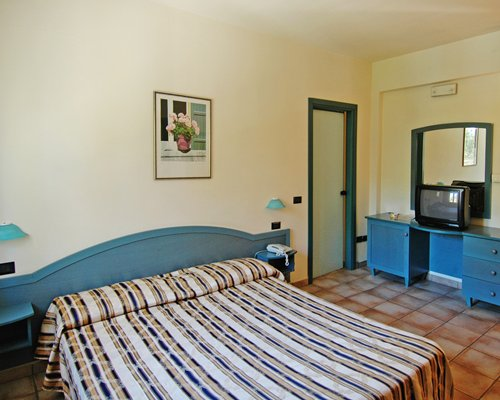 A well furnished bedroom with double bed and television.