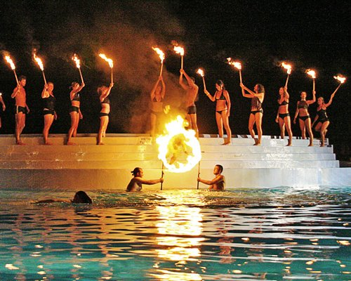 People entertaining with fire at an outdoor swimming pool.