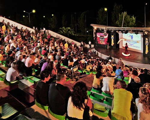 People watching the entertainment show at outdoor venue with a stage.