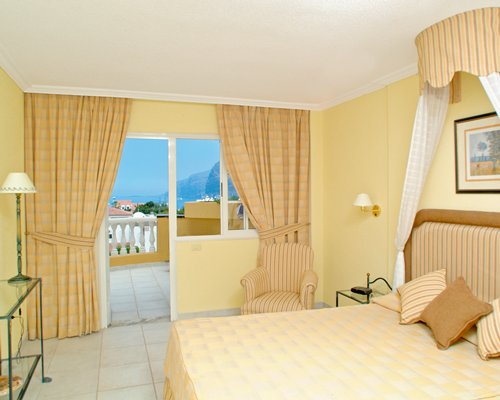 A well furnished bedroom with double bed and a balcony.