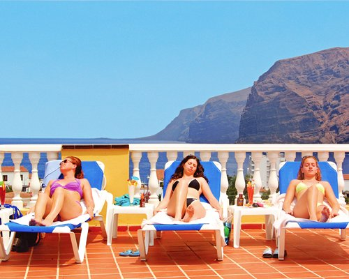 Women at chaise lounge chairs on a balcony alongside the ocean and mountains.