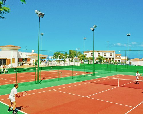 A view of two outdoor tennis courts.