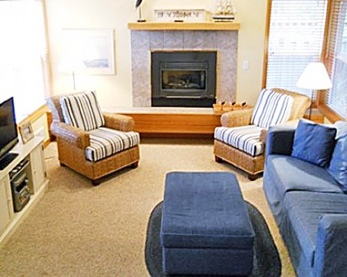 A well furnished living room with a television pull out sofa and a fireplace.