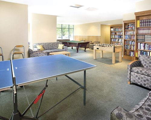 A recreational room with pool tables ping pong and foosball table.