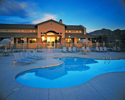 Exterior view of WorldMark Tucson Rancho Vistoso with outdoor swimming pool and chaise lounge chairs.