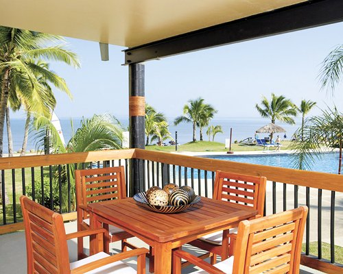 An outdoor dining area in the balcony with the beach view.