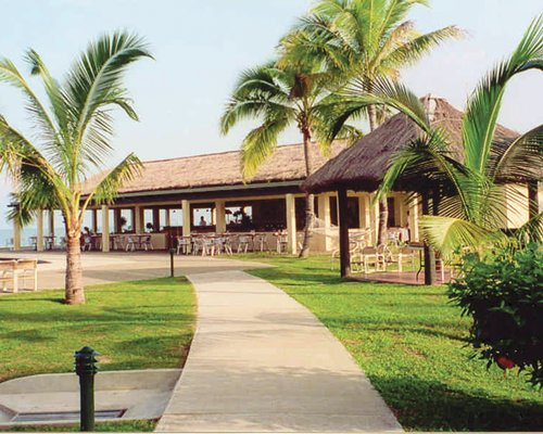 Scenic pathway to outdoor restaurant with thatched sunshades alongside the bay.