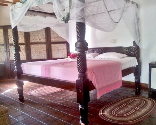 A bedroom with a four pillar cot.