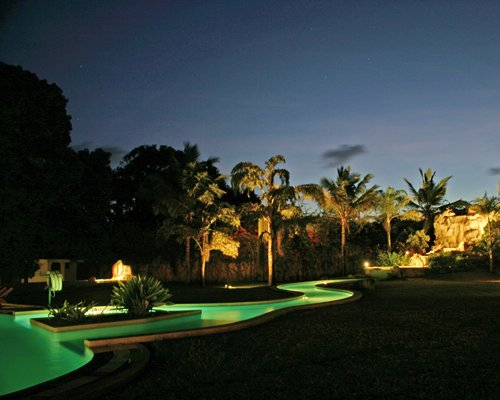 An outdoor pool alongside resort units at night.