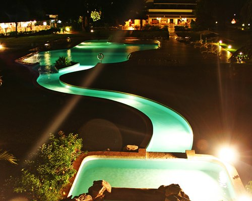 Outdoor swimming pool with chaise lounge chairs and sunshades at dusk.