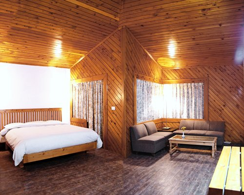 Wood paneled living room with a sofa and bed.