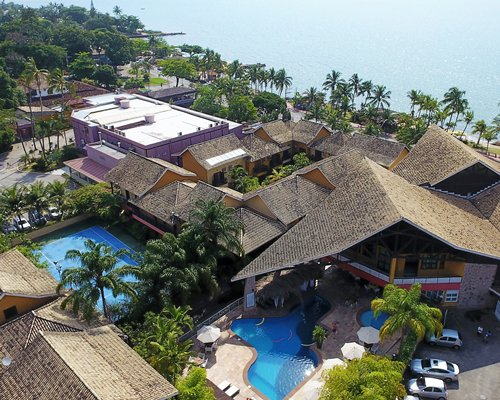 An aerial view of the resort properties surrounded by trees alongside the ocean.