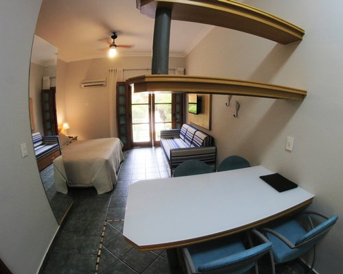 A well furnished bedroom with dining area and outdoor view.