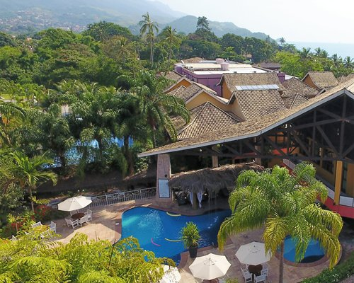An aerial view of the outdoor swimming pool with patio furniture alongside the resort.