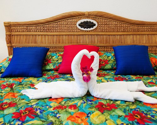 Two towels shaped as swan placed in a bed.