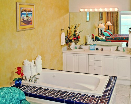 A well furnished bedroom with a bathtub and double sink vanity.