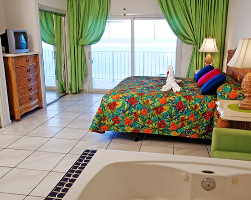 A well furnished bedroom with a queen bed bathtub and view of the sea.