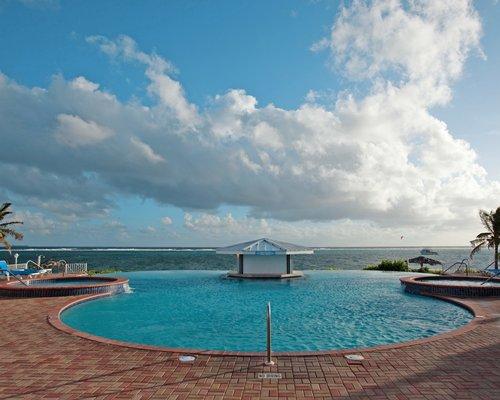 An outdoor swimming pool alongside the ocean.