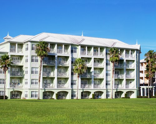 An exterior view of multi story resort units alongside a manicured lawn.