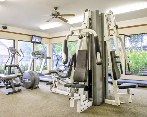 A well equipped fitness center with a television and an outside view.