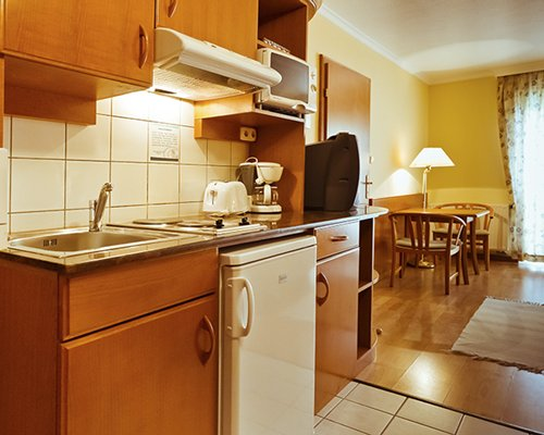A well equipped kitchen alongside the dining area with a television.