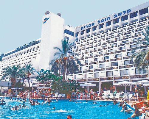 Exterior view of Club Hotel Tiberias with outdoor swimming pool chaise lounge chairs sunshades and palm trees.