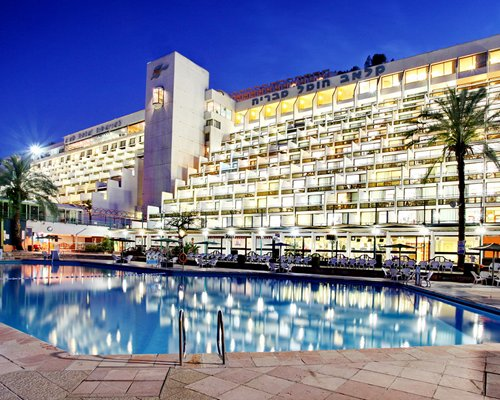 Night view of an outdoor swimming pool alongside the multi story Club Hotel Tiberias.