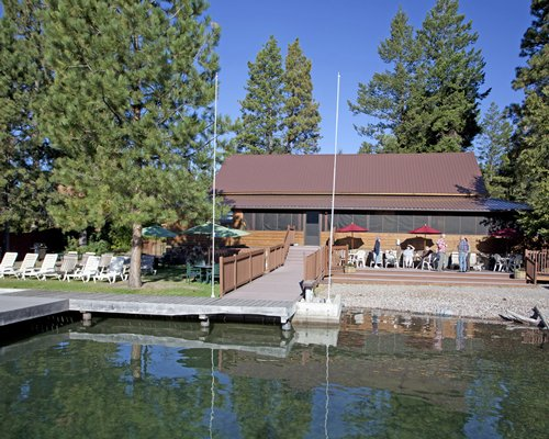 An exterior view of the resort surrounded by pine trees with a waterfront.
