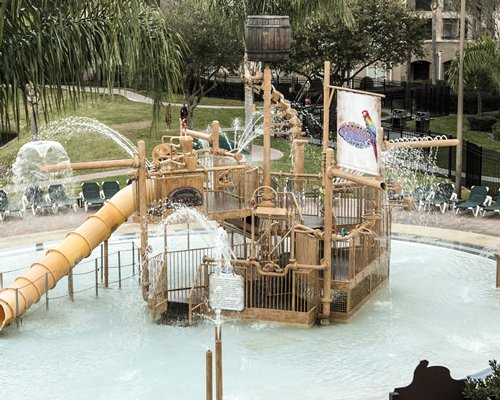 An outdoor water theme park with chaise lounge chairs.