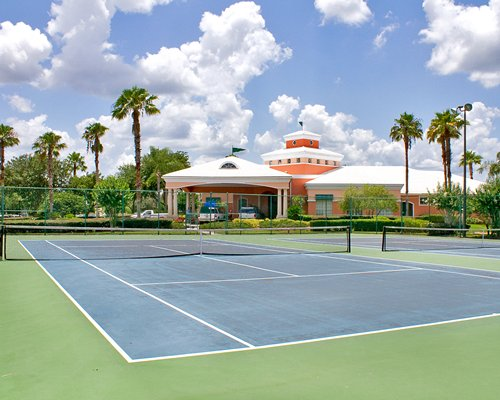 View of two outdoor tennis courts alongside resort units.
