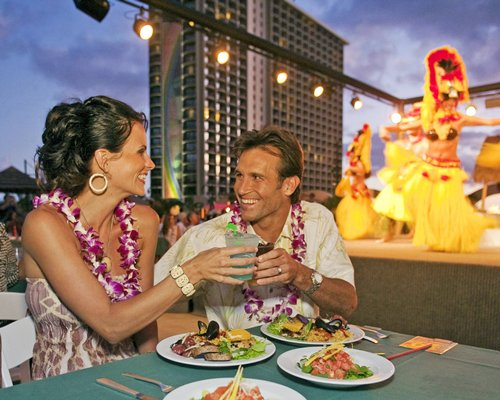 A couple at an outdoor dining and entertainment show having food and beverages.