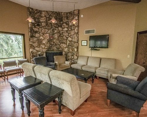 A well furnished living room with a television pull out sofa fireplace and an outside view.