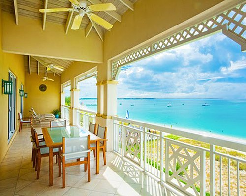 Outdoor dining in a balcony with a view of the beach.