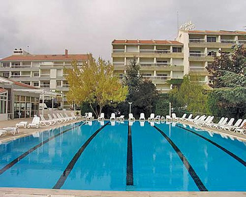 An outdoor swimming pool with chaise lounge chairs alongside the multi story resort units.