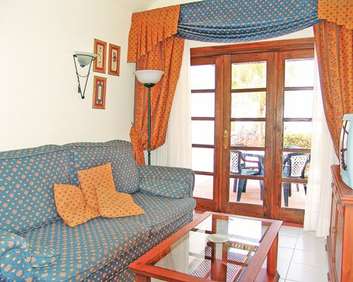 A well furnished living room with a television double pull out sofa and patio.