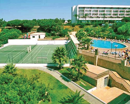 An outdoor tennis court and football court alongside the swimming pool.