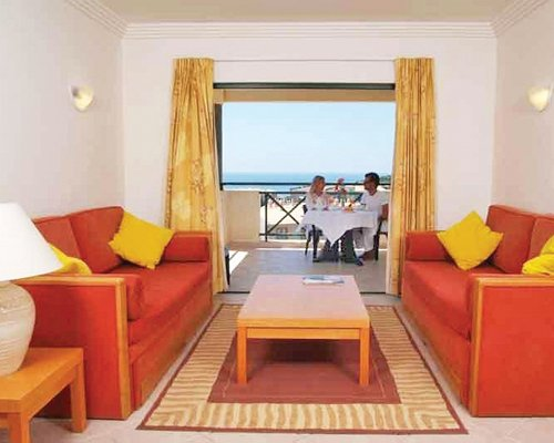 A well furnished living room with a couple on patio chairs at balcony.